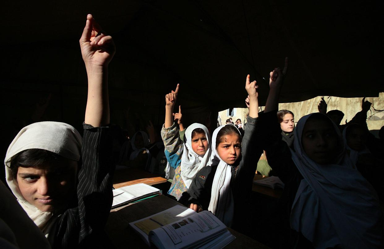 Afghan girls raise their hands during english class at the Bibi Mahroo high school in Kabul, Afghanistan November 22, 2006. (Paula Bronstein/Getty Images)