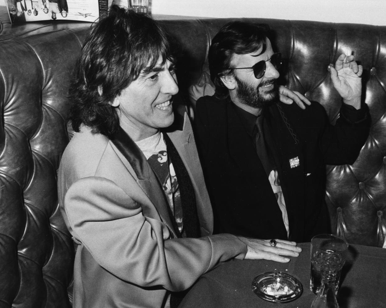 'The Beatles' musicians George Harrison (left) and Ringo Starr having a drink together in a booth, circa 1985. (Photo by Kevin Winter/Getty Images)