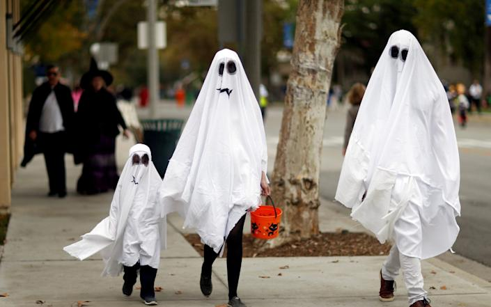 People wearing costumes walk during Halloween in Sierra Madre, California, - Mario Anzuoni/Reuters