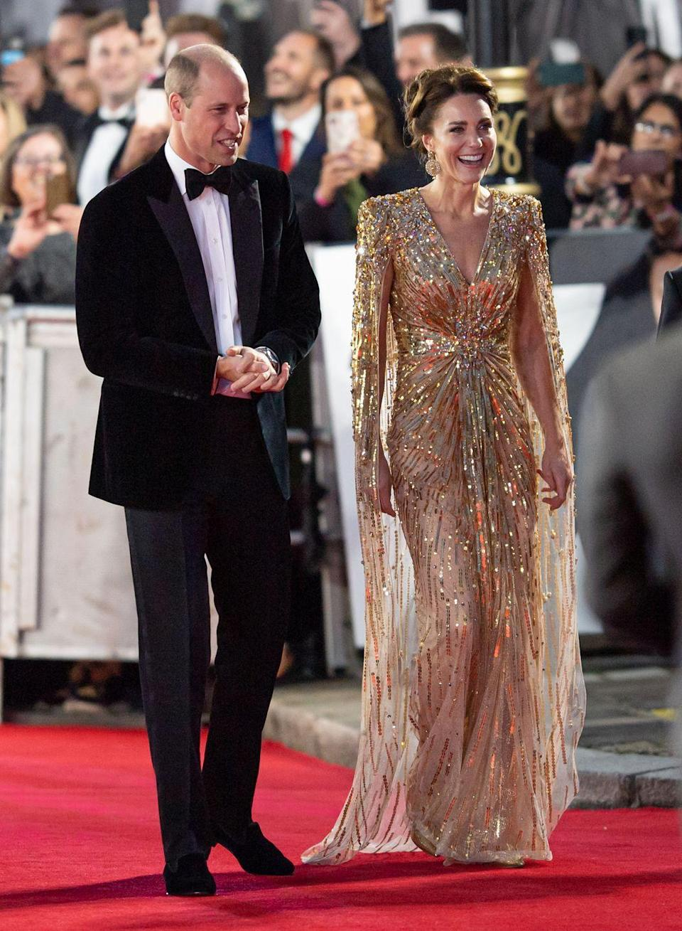 """<p>The Duchess of Cambridge stunned in a <a href=""""https://www.townandcountrymag.com/society/tradition/a37710183/kate-middleton-james-bond-premiere-gold-dress-photos/"""" rel=""""nofollow noopener"""" target=""""_blank"""" data-ylk=""""slk:gold, embellished Jenny Packham gown"""" class=""""link rapid-noclick-resp"""">gold, embellished Jenny Packham gown</a>, complete with an attached cape. </p>"""