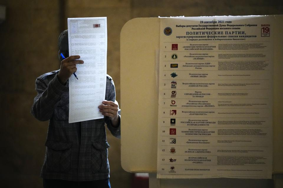 A man reads his ballot at a polling station during the Parliamentary elections in Moscow, Russia, Sunday, Sept. 19, 2021. Russia has begun the third day of voting for a new parliament that is unlikely to change the country's political complexion. There's no expectation that United Russia, the party devoted to President Vladimir Putin, will lose its dominance in the State Duma. (AP Photo/Alexander Zemlianichenko)