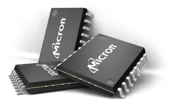 Three Micron semiconductor chips loosely stacked near each other against a white surface.