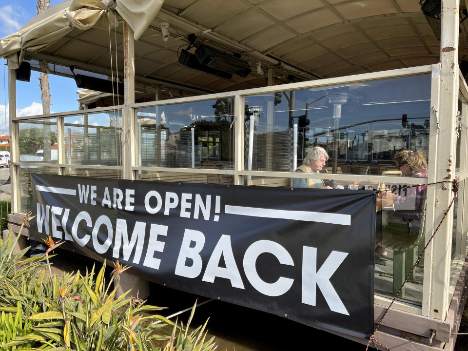 "Diners eat on the patio of a restaurant behind a large sign reading ""We are open! Welcome back"""