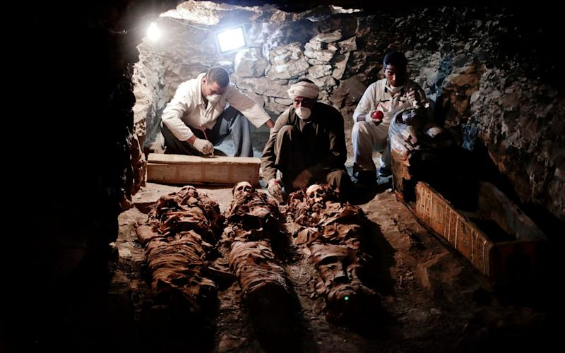 Archaeologists work on mummies found in the New Kingdom tomb that belongs to a royal goldsmith in Luxor - AP