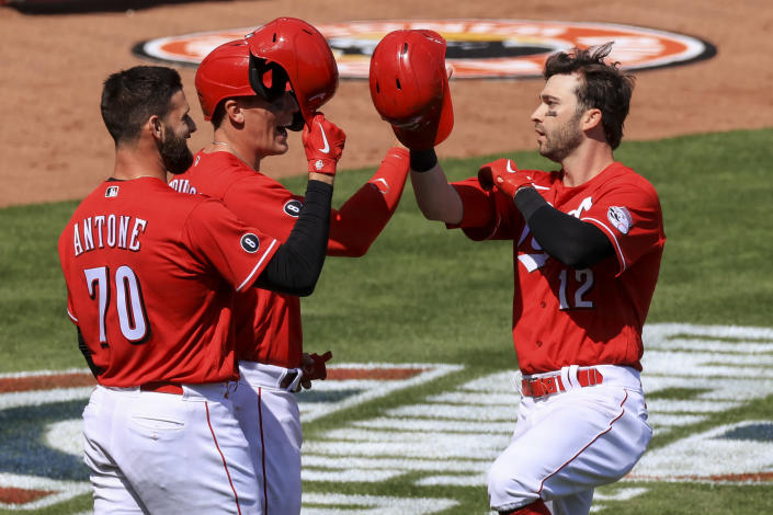 Cincinnati Reds' Tejay Antone, left, and Tyler Stephenson, middle, celebrate the three-run home run hit by Tyler Naquin, right, during the sixth inning of a baseball game against the St. Louis Cardinals in Cincinnati, Sunday, April 4, 2021. (AP Photo/Aaron Doster)