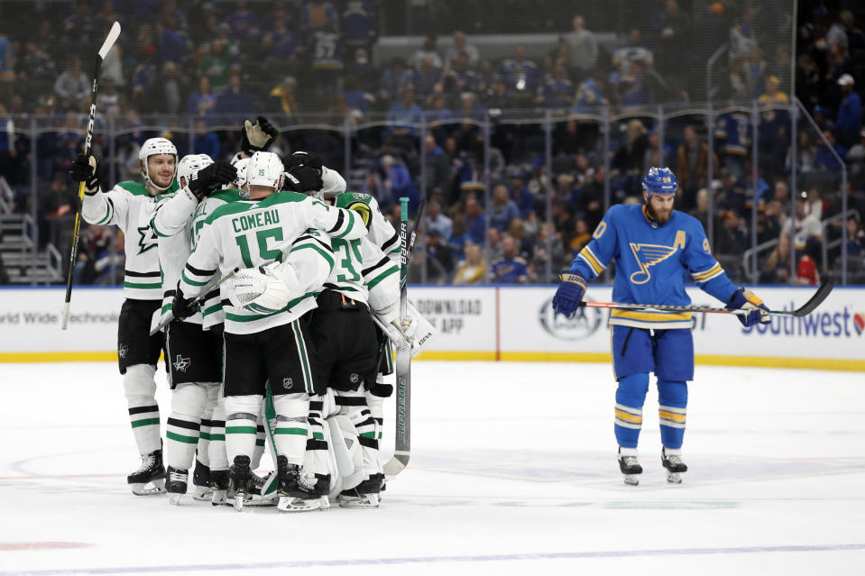 Members of the Dallas Stars celebrate as St. Louis Blues' Ryan O'Reilly, right, skates past following an NHL hockey game Saturday, Feb. 8, 2020, in St. Louis. The Stars won 3-2 in overtime. (AP Photo/Jeff Roberson)