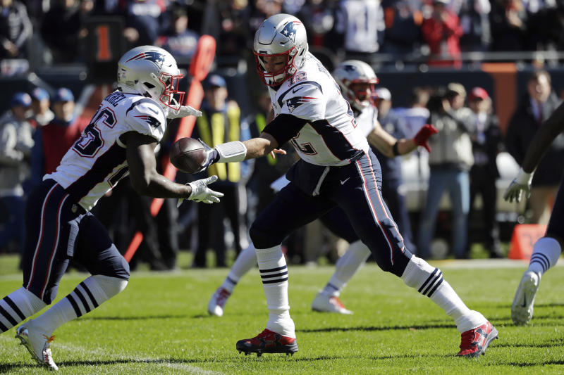New England Patriots quarterback Tom Brady (12) hands off the ball to running back Sony Michel (26) during the first half of an NFL football game against the Chicago Bears Sunday, Oct. 21, 2018, in Chicago. (AP Photo/Nam Y. Huh)