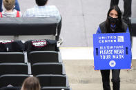 An usher holds a sign reminding fans about COVID-19 precautions, during the first half of an NBA basketball game between the Boston Celtics and the Chicago Bulls in Chicago, Friday, May 7, 2021. (AP Photo/Nam Y. Huh)