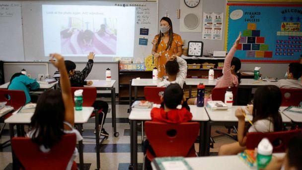 PHOTO: Teacher Mary Yi works with fourth grade students at the Sokolowski School, where students and teachers are required to wear masks because of the COVID-19 pandemic, in Chelsea, Mass., Sept. 15, 2021. (Brian Snyder/Reuters)