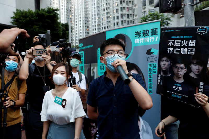 FILE PHOTO: Pro-democracy activists Tiffany Yuen Ka-wai and Joshua Wong attend a campaigning during primary elections aimed for selecting democracy candidates, in Hong Kong