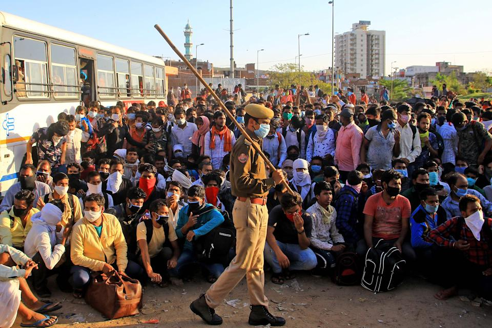 Security personnel with migrants who are waiting to board a bus to their native places in Jaipur, Rajasthan, March 28,2020. (Photo: NurPhoto via Getty Images)