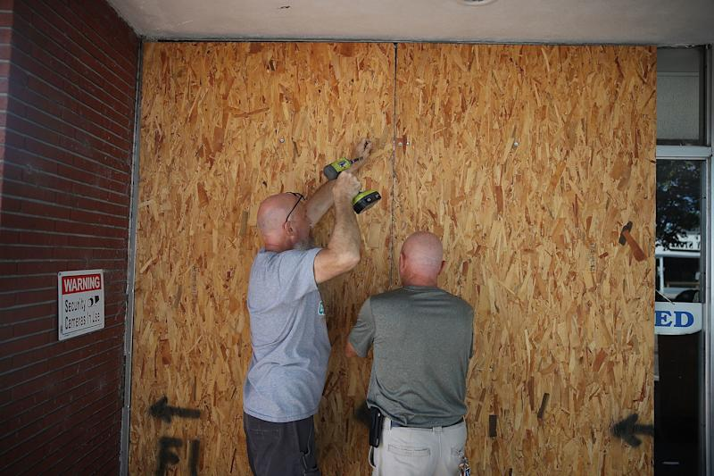 Jay Schwartz, left, and Michael Schwartz secure plywood over the windows of their business ahead of the arrival of Hurricane Florence on Tuesday in Myrtle Beach.