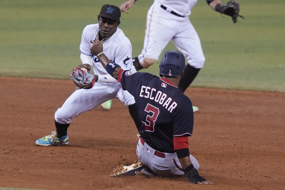 Washington Nationals' Alcides Escobar (3) is safe on second as Miami Marlins second baseman Jazz Chisholm Jr. is late with the tag during the sixth of a baseball game, Tuesday, Sept. 21, 2021, in Miami. (AP Photo/Marta Lavandier)