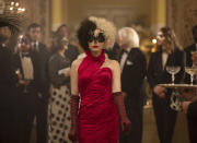 """This image released by Disney shows Emma Stone in a scene from """"Cruella."""" Costumes for the film were designed by Oscar winning designer Jenny Beavan. (Laurie Sparham/Disney via AP)"""