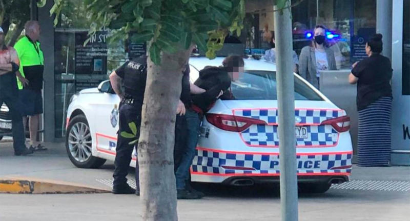 A man is held against a police car by officers in Booval.