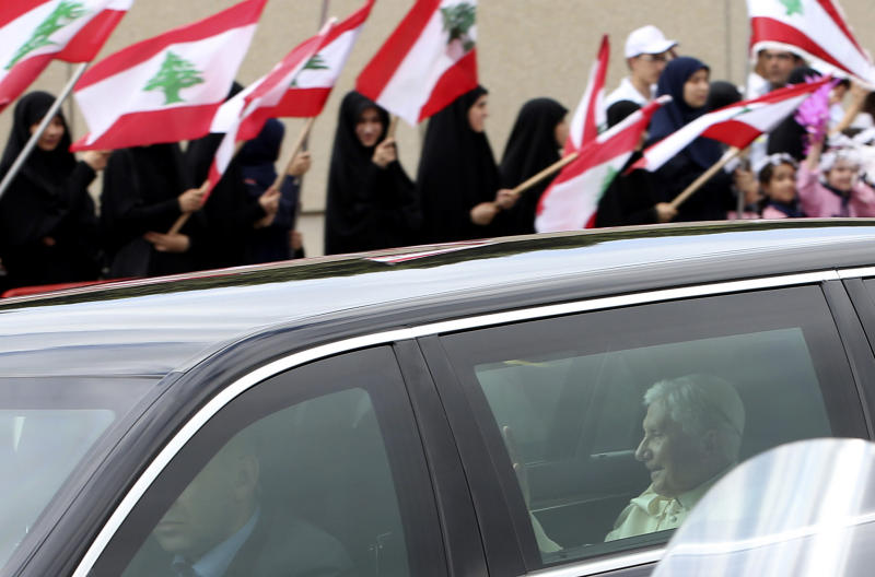 "Veiled Muslim women wave Lebanese flags as they welcome Pope Benedict XVI, who is seen inside a car outside Rafik Hariri international airport in Beirut, Lebanon, Friday Sept. 14, 2012. Pope Benedict XVI arrived in Lebanon on Friday to urge peace at a time of great turmoil in the Middle East, saying the import of weapons to Syria during the country's civil war is a ""grave sin."" (AP Photo/Hussein Malla)"
