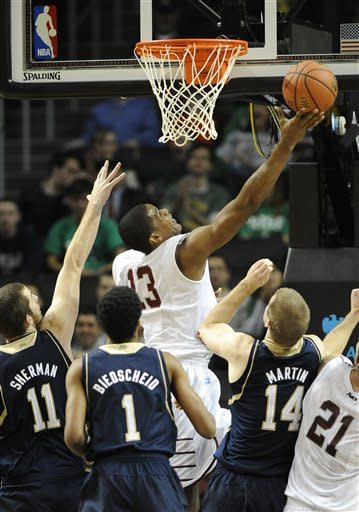 Saint Joseph's Ronald Roberts Jr. (13) leaps above Notre Dame's Garrick Sherman (11), Cameron Biedscheid (1) and Scott Martin (14) to score a basket in the first half of the Coaches vs. Cancer Classic basketball game on Friday, Nov., 16, 2012, at Barclays Center in New York. (AP Photo/Kathy Kmonicek)