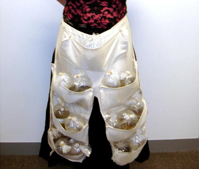 """<p>A woman on a flight from Singapore to Melbourne shows the 51 live tropical fish hidden in a specially designed apron under her skirt in this handout photograph from the Australian Customs Service on June 3, 2005. Customs officers became suspicious after hearing """"flipping"""" noises coming from the vicinity of her waist, and an examination revealed 15 plastic water-filled bags holding concealed fish. (Photo: Handout/Australian Customs Service/Reuters) </p>"""