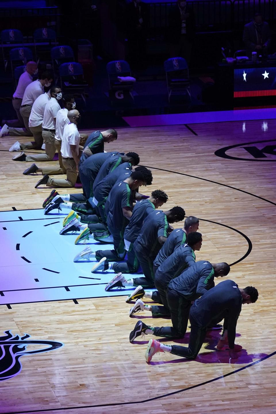 The Miami Heat team kneels during the playing of the National Anthem before an NBA basketball game against the Boston Celtics, Wednesday, Jan. 6, 2021, in Miami. (AP Photo/Marta Lavandier)