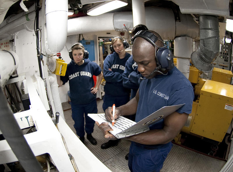 In this June 23, 2011 photo, U.S. Coast guard Academy, 1st Class, Cadet Orlando Morel, foreground, reviews a logbook in the generator room aboard the Coast Guard Cutter Eagle. Morel was 6 years old when he and his mother were rescued by the Coast Guard while leaving Haiti. Morel, now of Rockville, Md., will graduate Wednesday, May 16, 2012, from the Coast Guard Academy in New London, Conn. (AP Photo/ U.S. Coast Guard, NyxoLyno Cangemi)