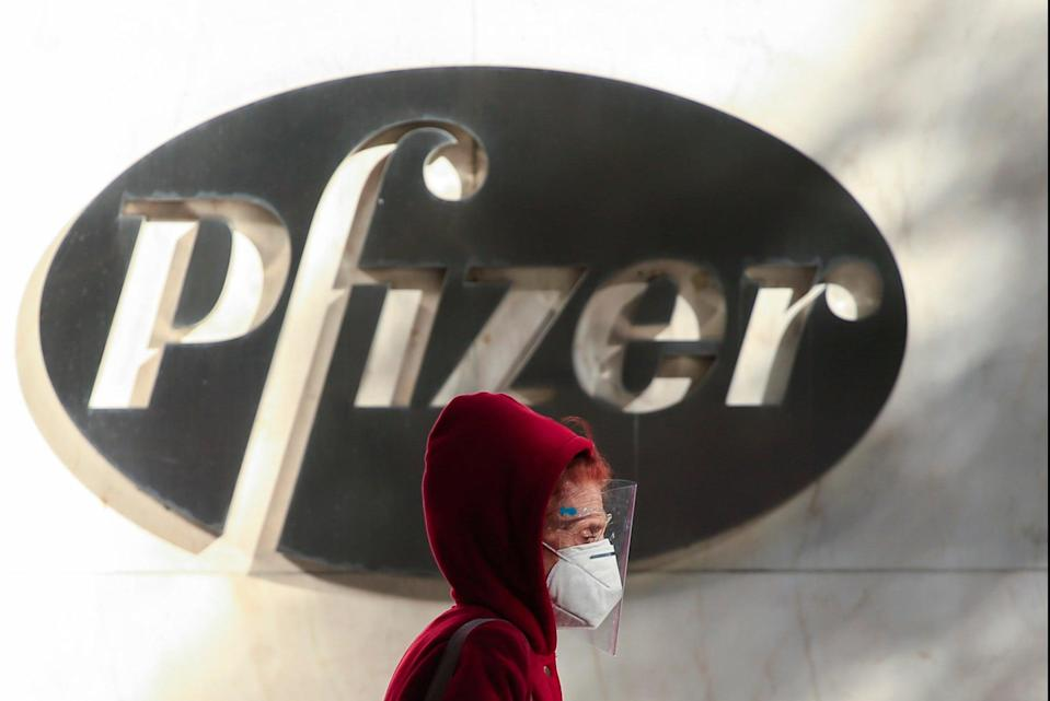 A woman wears a facemask as she walks by the Pfizer world headquarters in New York (AFP via Getty Images)