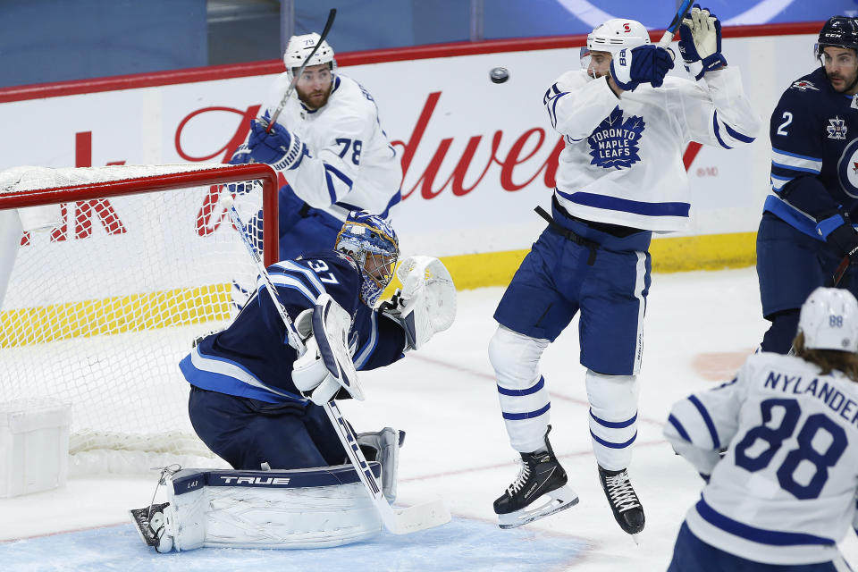 Toronto Maple Leafs' Nick Foligno (71) deflects the puck toward Winnipeg Jets goaltender Connor Hellebuyck (37) during the second period of an NHL hockey game Friday, May 14, 2021, in Winnipeg, Manitoba. (John Woods/The Canadian Press via AP)