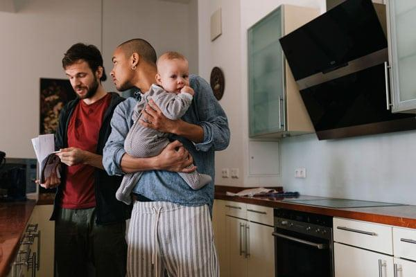 couple talking in kitchen, one of the Fathers is holding a baby in his arms.