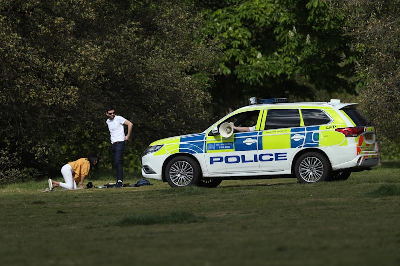 Police officers in a patrol car move on sunbathers in Greenwich Park, London, as the UK continues in lockdown to help curb the spread of the coronavirus.