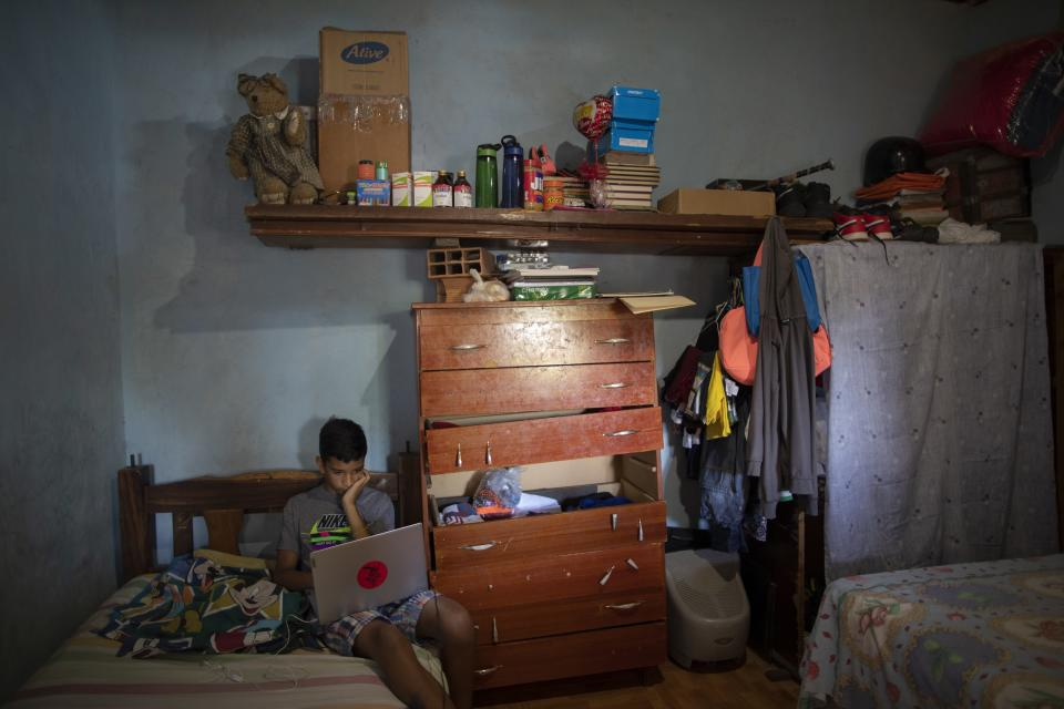Samuel Andres Mendoza sits in his room with a laptop, gifted to him by his social media followers, at his home in Barquisimeto, Venezuela, Tuesday, March 2, 2021. After the 14-year-old tweeted to sell his drawings to buy food, an artist gave him a scholarship to study drawing, and social media followers sent him a set of artists' pencils and food. (AP Photo/Ariana Cubillos)
