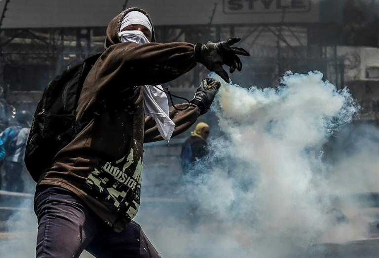 A demonstrator protesting against President Nicolas Maduro's government throws back a tear gas grenade at riot police in Caracas on April 10, 2017