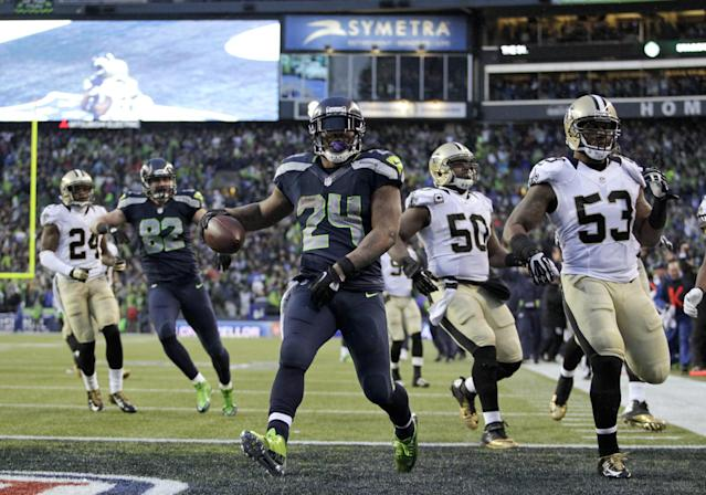 Seattle Seahawks running back Marshawn Lynch (24) arrives in the end zone with a 31-yard touchdown during the fourth quarter of an NFC divisional playoff NFL football game against the New Orleans Saints in Seattle, Saturday, Jan. 11, 2014. (AP Photo/John Froschauer)