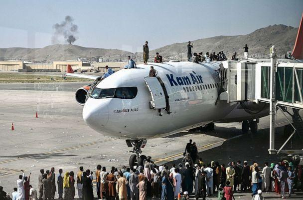 PHOTO: Afghan people climb atop a plane as they wait at the Kabul airport in Kabul, Afghanistan, Aug. 16, 2021. (Wakil Kohsar/AFP via Getty Images)
