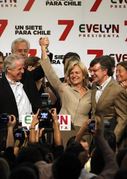 "Chile's presidential candidate Evelyn Matthei holds hands up with her husband Jorge Desormeaux, left, as she greets supporters at her campaign headquarters in Santiago, Chile, Sunday, Nov. 17, 2013. Former President Michelle Bachelet won nearly twice as many votes as her closest rival Matthei in Chile's presidential election Sunday, but she fell short of the outright majority needed to avoid a Dec. 15 runoff. ""Going into a second round is certainly a triumph,"" an exultant Matthei told supporters. At right is Matthey's campaign spokesman Joaquin Lavin,.(AP Photo/Victor Ruiz Caballero)"