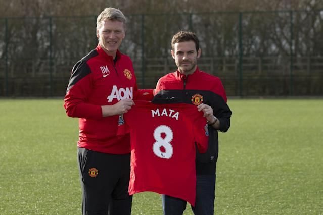 Manchester United's new signing Juan Mata, right, displays his new shirt alongside manager David Moyes before a press conference at the team's Carrington training ground, Manchester, England, Monday, Jan. 27, 2014. With Manchester United in danger of missing out on the Champions League next season, Juan Mata's arrival at Old Trafford for a club record fee of 37.1 million pounds ($61.2 million) is certainly an emergency move. But it also marks the first step in the rebuilding process of England's most titled club. After a botched transfer campaign last summer that was followed by the club's lackluster first half of the season, United now looks determined to allow manager David Moyes the opportunity to build his own team.(AP Photo/Jon Super)