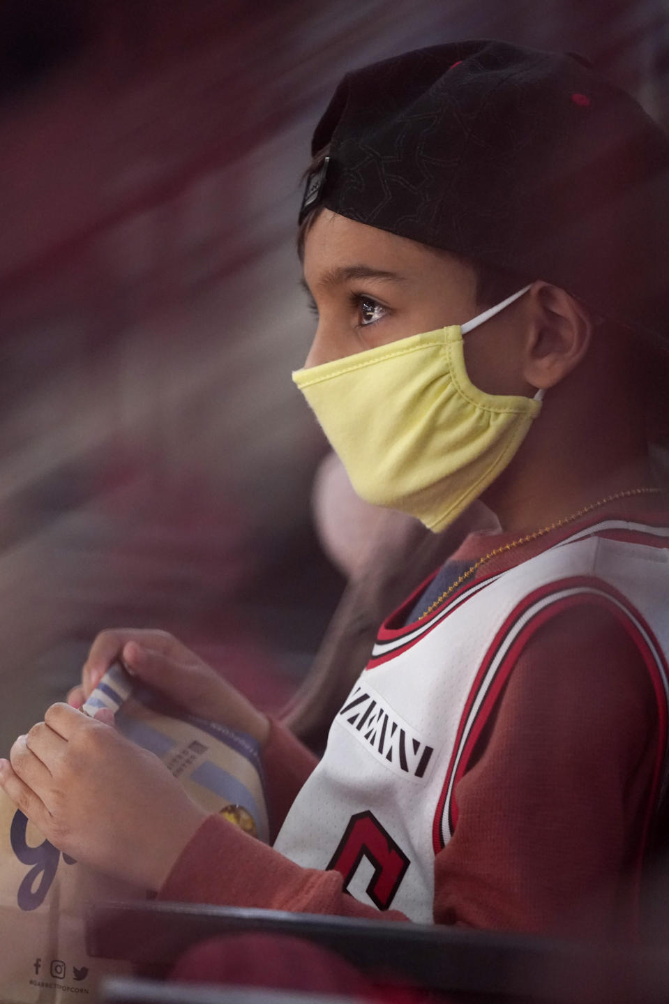 Jaxen Desai, 7, wears mask as he watches the first half of an NBA basketball game between the Boston Celtics and the Chicago Bulls in Chicago, Friday, May 7, 2021. (AP Photo/Nam Y. Huh)