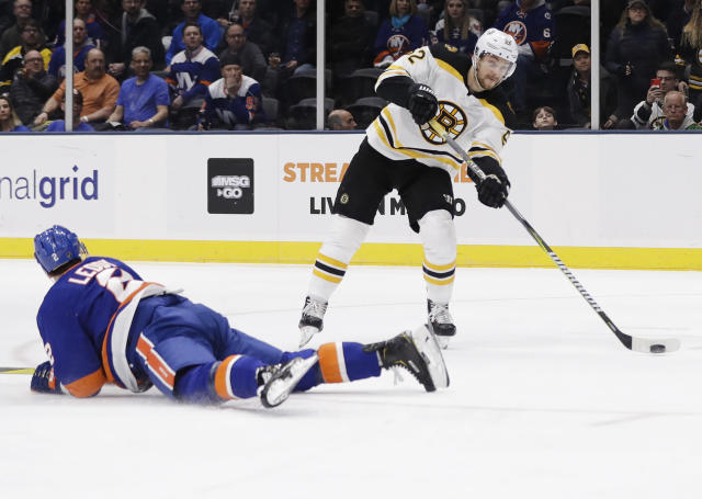Boston Bruins' Sean Kuraly (52) drives past New York Islanders' Nick Leddy (2) during the first period of an NHL hockey game Tuesday, March 19, 2019, in Uniondale, N.Y. (AP Photo/Frank Franklin II)