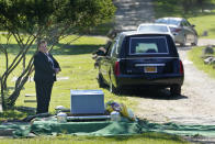 Shannon Walters, of the John Vincent Scalia Home for Funerals, stands by as people leave after the burial of four people at a cemetery in the Staten Island borough of New York, Thursday, June 17, 2021. The deceased died during the coronavirus pandemic and were being stored at a temporary morgue in Brooklyn. The facility is out of sight and mind for many as the city celebrates its pandemic progress but stands as a reminder of the loss, upheaval and wrenching choices the virus inflicted in one of its deadliest U.S. hotspots. (AP Photo/Seth Wenig)