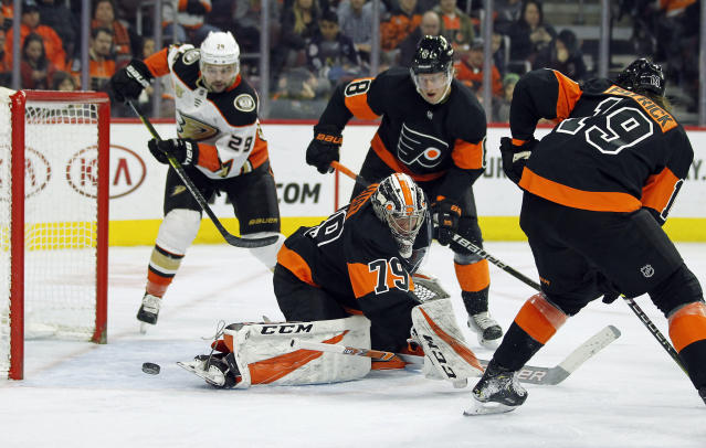 The puck goes past Philadelphia Flyers goalie Carter Hart, but wide of the net, during the third period of an NHL hockey game against the Anaheim Ducks, Saturday, Feb. 9, 2019, in Philadelphia. Looking on, from rear left, are Ducks' Devin Shore, Flyers' Robert Hagg and right, Nolan Patrick. The Flyers won 6-2. (AP Photo/Tom Mihalek)