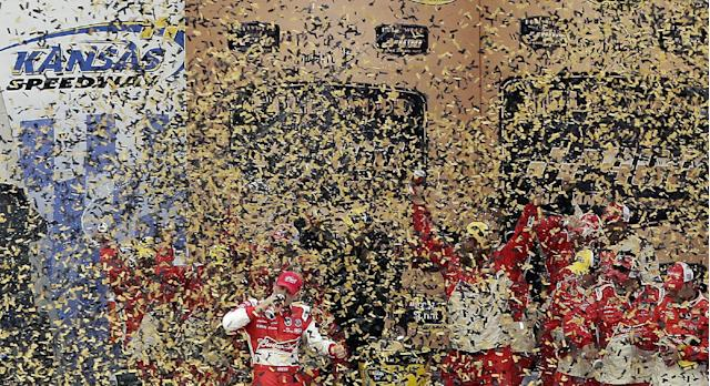 Driver Kevin Harvick celebrates in victory lane after winning the NASCAR Sprint Cup series auto race at Kansas Speedway in Kansas City, Kan., Sunday, Oct. 6, 2013. (AP Photo/Charlie Riedel)