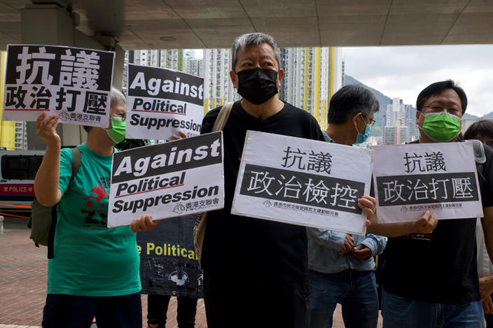 Pro-democracy activist Lee Cheuk-yan, center, holds placards as he arrives at a court in Hong Kong Thursday, April 1,2021. Seven pro-democracy advocates, including media tycoon Jimmy Lai and veteran of the city's democracy movement Martin Lee, are expected to be handed a verdict for organizing and participating in an illegal assembly during massive anti-government protests in 2019 as Hong Kong continues its crackdown on dissent. (AP Photo/Vincent Yu)
