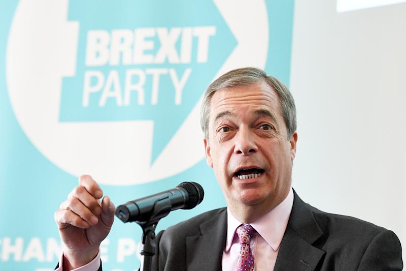 Nigel Farage speaks in front of a Brexit party logo.
