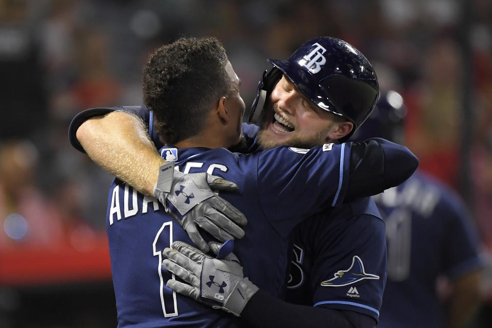 Tampa Bay Rays' Austin Meadows, right, gets a hug from Willy Adames after hitting a two-run home run during the third inning of the team's baseball game against the Los Angeles Angels on Friday, Sept. 13, 2019, in Anaheim, Calif. (AP Photo/Mark J. Terrill)