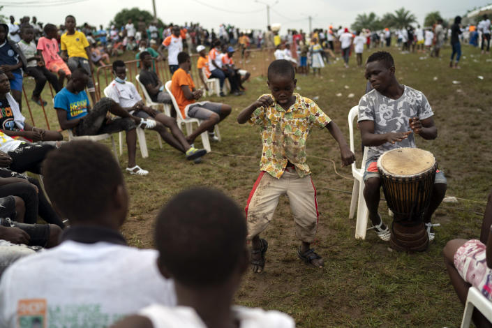 A boy dances as a supporter plays an african percussion instrument before the arrival of the Ivory Coast President Alassane Ouattara at a rally in Anyama, in the outskirts of Abidjan, Ivory Coast, Wednesday, Oct. 28, 2020. Ouattara, who first came to power after the 2010 disputed election whose aftermath left more than 3,000 people dead, is now seeking a third term in office. The candidate maintains that he can serve a third term because of changes to the country's constitution, though his opponents consider his candidacy illegal. (AP Photo/Leo Correa)