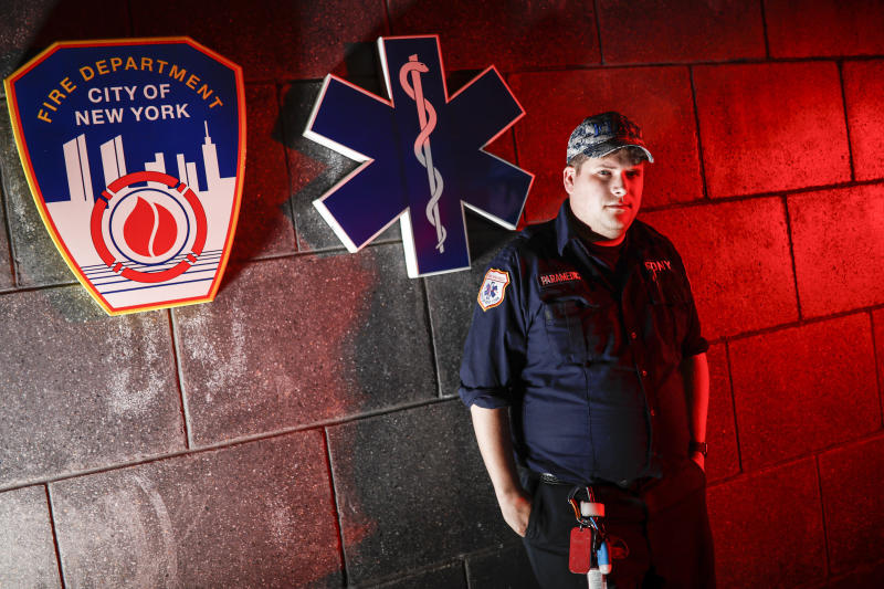 Paramedic Travis Kessel is photographed outside his station house after working a shift amid the COVID-19 pandemic, Monday, April 6, 2020, in the Bronx borough of New York. Kessel never imagined his work could hurt this much. He loves his career in emergency services. It's even how he met his wife, an emergency room nurse. But now he worries about the toll the new coronavirus is taking on both of them and their colleagues. (AP Photo/John Minchillo)