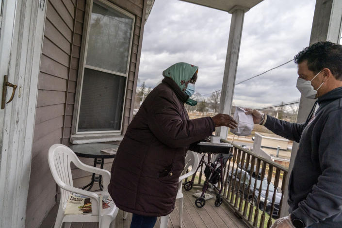 Dominga Costa, 88, left, receives a Thanksgiving dinner and some cookies from Meals on Wheels volunteer, Ted Fischer, Wednesday, Nov. 25, 2020, at her home in Providence, R.I. As more at-risk seniors find themselves unable to leave their homes during the COVID pandemic, Meals on Wheels has been delivering on average 4,000 meals per day up from their pre-pandemic average of 1200. (AP Photo/David Goldman)