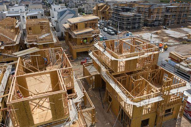 PHOTO: Contractors work on single-family homes under construction in the Cadence Park development in Irvine, Calif., April 14, 2021. (Bloomberg via Getty Images)