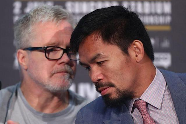 Freddie Roach (L) consults with Manny Pacquiao during a news conference. (Getty)