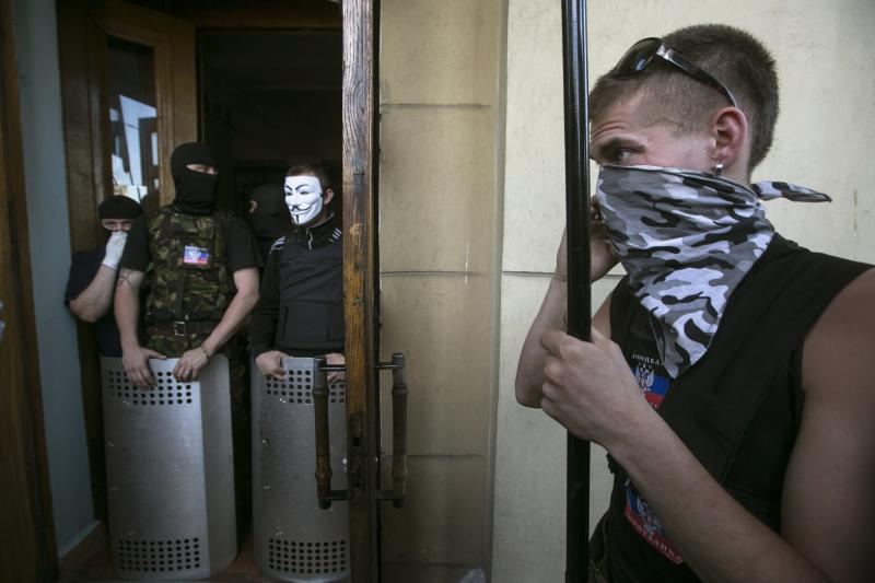 Pro-Russian activists block the entrance to a television station in Donetsk, eastern Ukraine April 27, 2014. Pro-Russian separatists on Sunday seized control of the offices of regional state television in the eastern Ukrainian city of Donetsk, a Reuters reporter outside the building said. The reporter said four separatists in masks, with truncheons and shields, were standing at the entrance to the building controlling access, while more separatists in camouflage fatigues could be seen inside. REUTERS/Baz Ratner (UKRAINE - Tags: MEDIA CIVIL UNREST POLITICS)