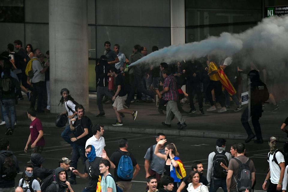 Un manifestante descarga un extintor contra los mossos (Photo by LLUIS GENE/AFP via Getty Images)