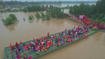 Mass evacuation by boat bridge in flood-hit Chinese villages